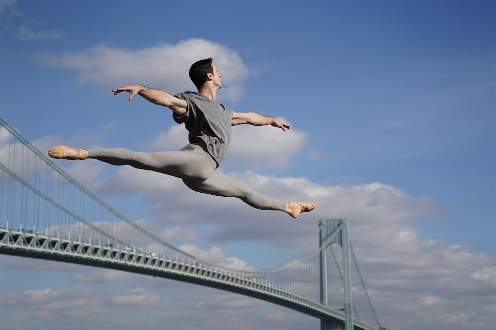 man-in-gray-mid-jump-with-bridge-alpha-7III