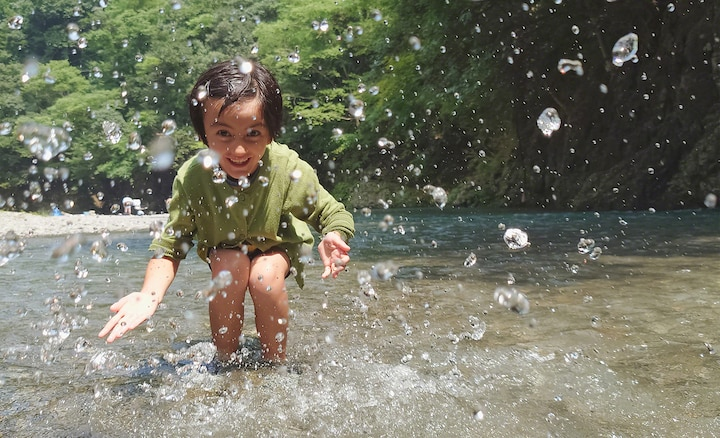 Little girl playing in a stream, splashing water at the camera