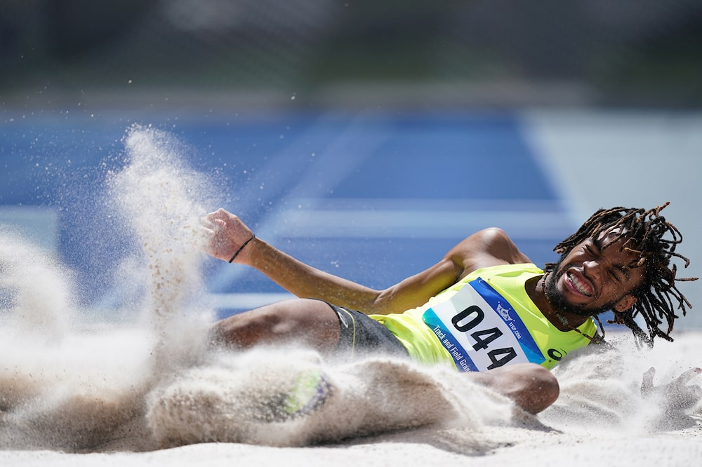 long-jump-sprinter-slides-across-sand-alpha-9